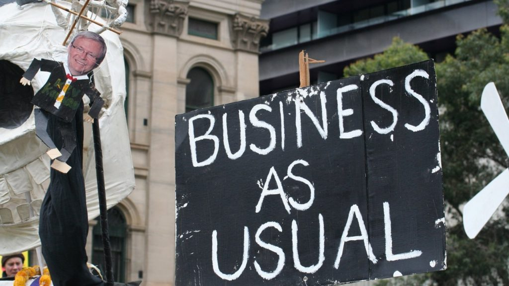 "Banner in a protest displaying the text ""Business as usual""."