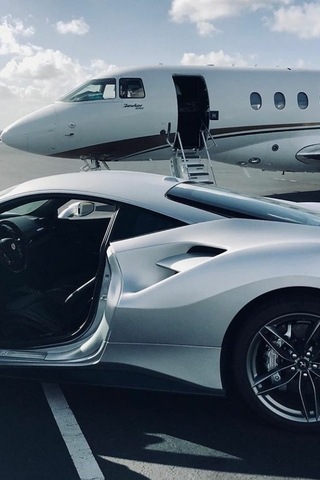 An expensive sports car in the foreground with a private jet in the background.